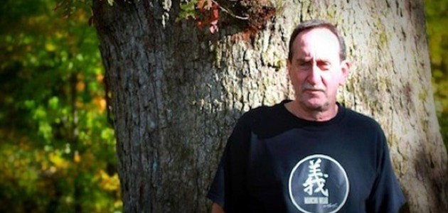 Garry Katz in Black Tshirt standing in front of a tree